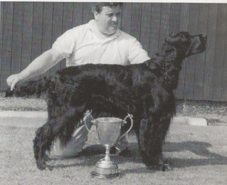 man with dog with silver trophy in front of them