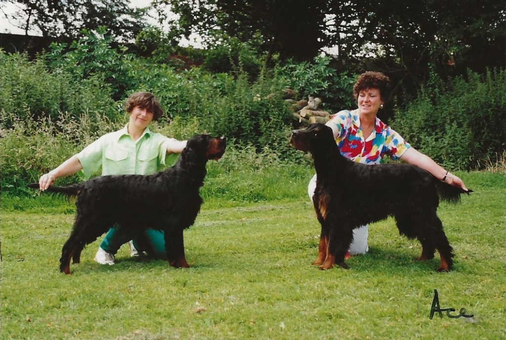 two women posing black and tans dogs